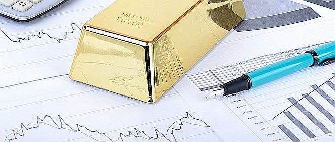 Gold bar on stock figures with calculator and pen