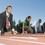 Full length of four multiethnic businesspeople at starting position on race track